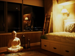 A combination guest bedroom and massage area features spotlighting on a ceramic buddha and dual purpose bedside task lighting