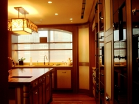 Kitchen featuring LED linear lighting built into wine-rack, wall grazing halogen accent lights, and decorative chandelier